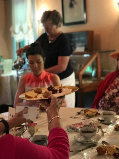 Mickey Carr, Board Member serves tea as the table enjoys assorted desserts.